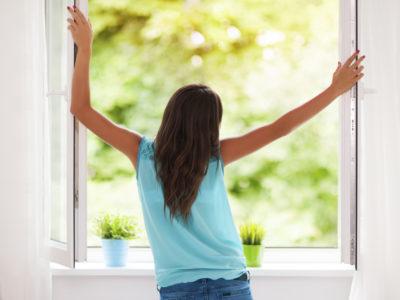 frau vor offenem Fenster